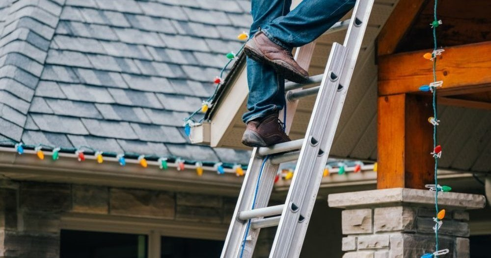 Man on a ladder installing outdoor Christmas lights.